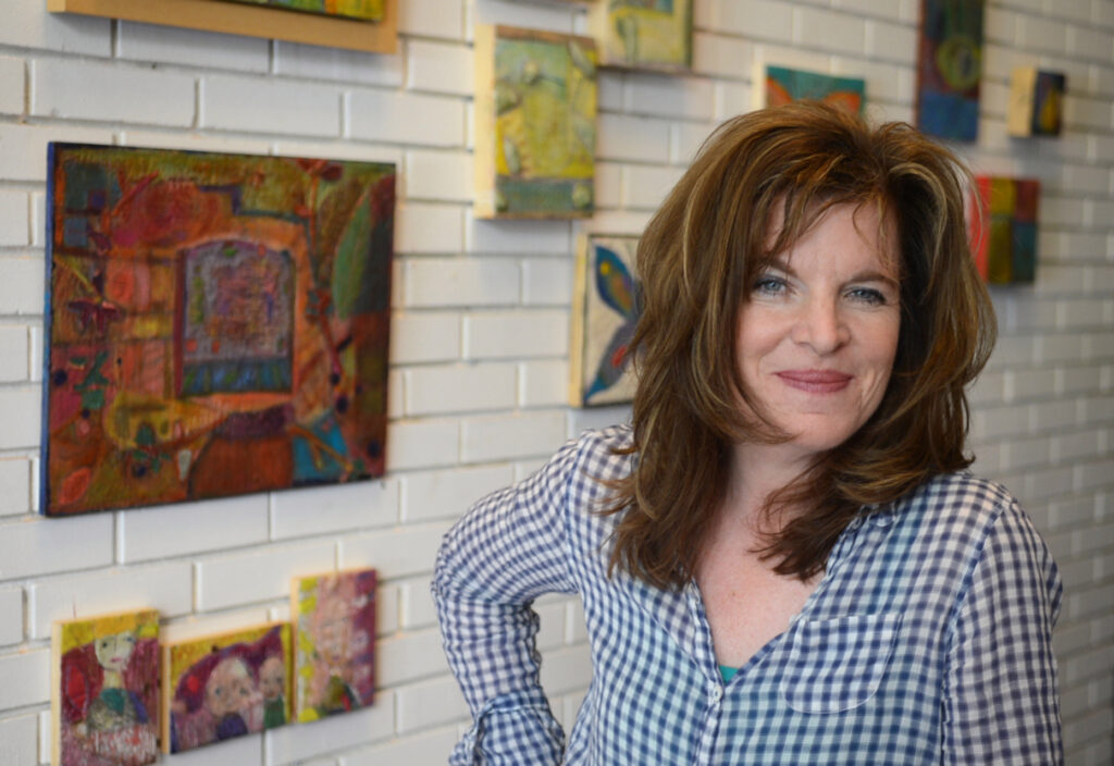 "Cynthia Pepper stands with some of the pieces in her show ""Collections and Selections"" in the lobby of Crome Architecture on Thursday, May 1, 2014, in San Rafael, Calif. The show features encaustic wax paintings and will hang through May. (Frankie Frost/Marin Independent Journal)"